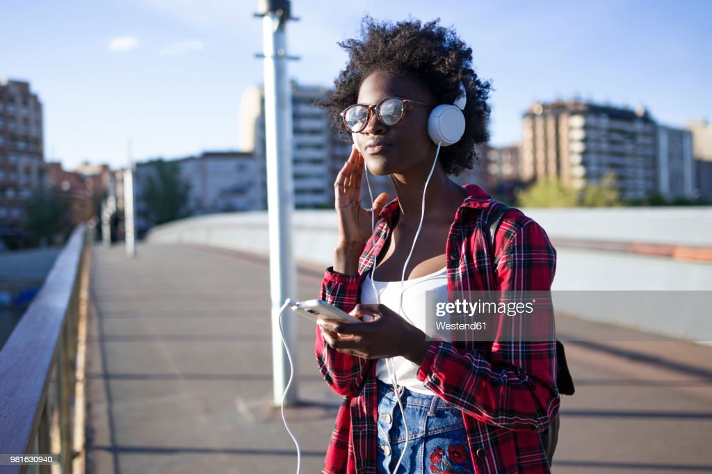 Portrait of young woman on a bridge listening music with headphones : Stock-Foto