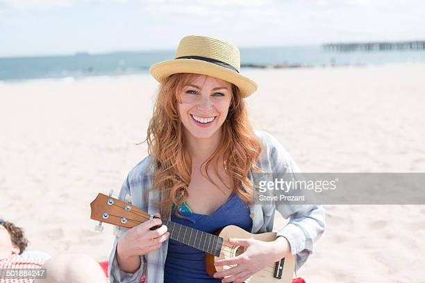 Portrait of young woman on beach playing ukulele