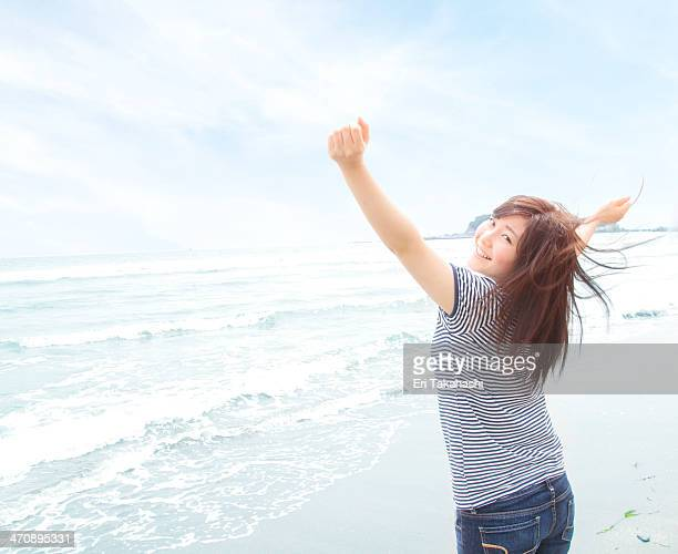 Portrait of young woman on beach with arms raised, looking over shoulder