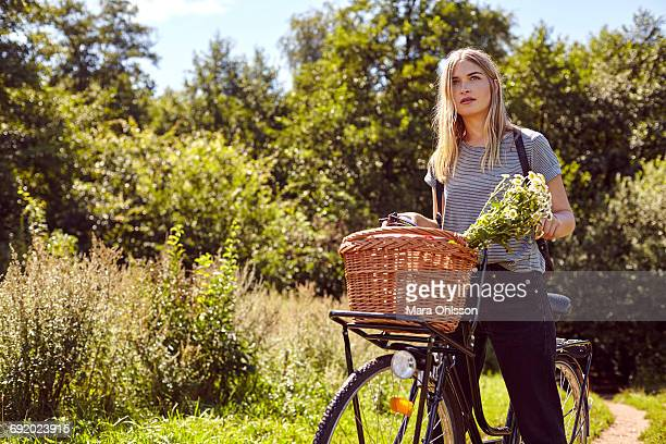 Portrait of young woman on bicycle gazing from rural dirt track