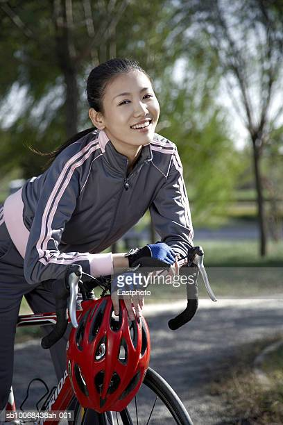 Portrait of young woman on bike in park