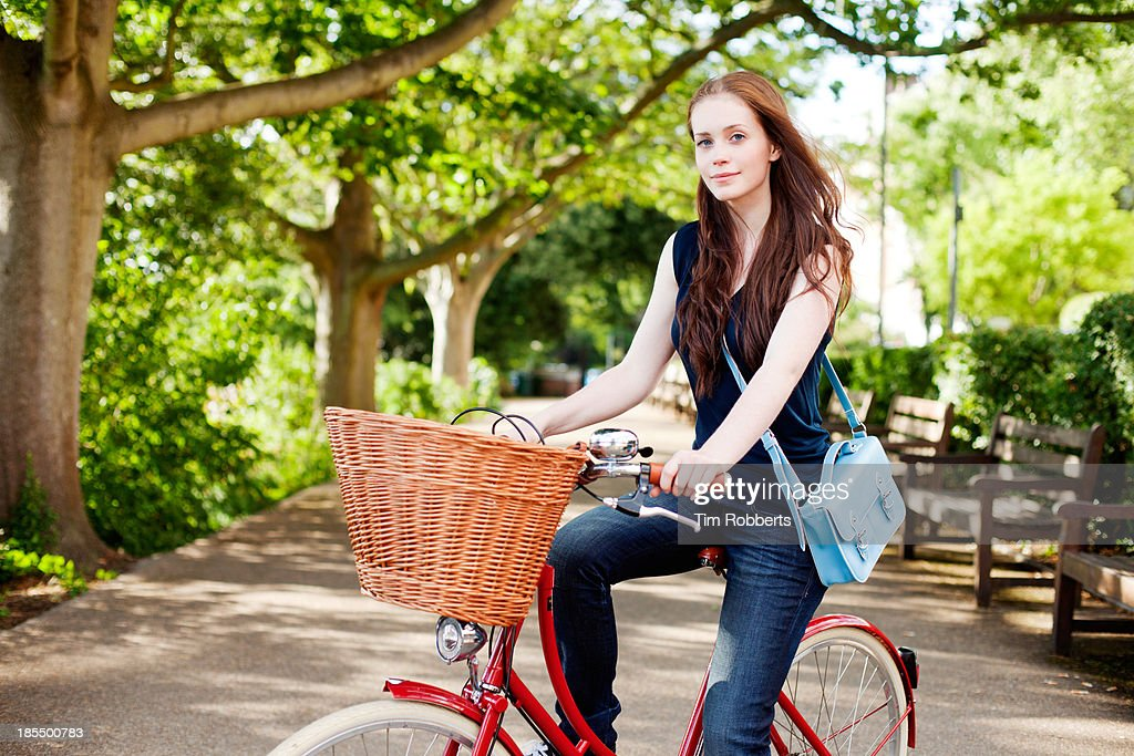 Portrait of young woman on bike with trees. : Stock Photo
