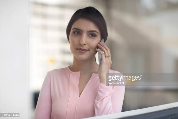Portrait of young woman on cell phone in the office