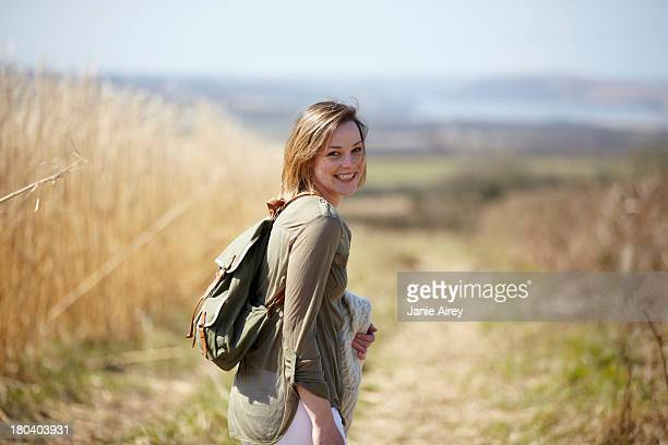 portrait of young woman on dirt track next to field of reeds - bob frisur stock-fotos und bilder
