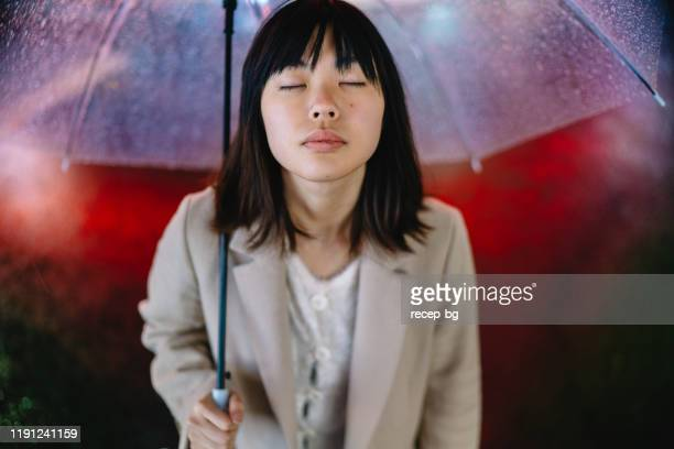 portrait of young woman on rainy day at night with her eys closed - in the center stock pictures, royalty-free photos & images