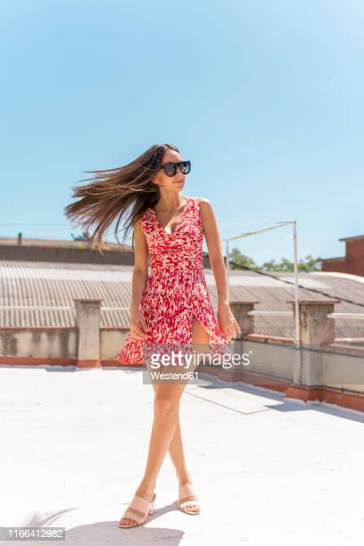 portrait of young woman on roof top wearing fashionable summer dress tossing her hair - open toe stock pictures, royalty-free photos & images