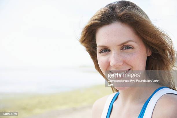 Portrait of young woman on seashore, smiling