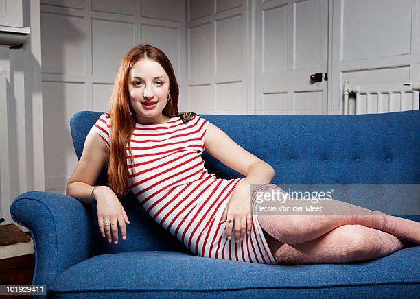 portrait of  young woman on sofa. - striped dress stock pictures, royalty-free photos & images