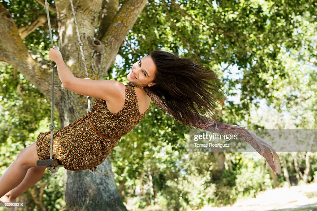 Portrait of young woman on swing : Bildbanksbilder