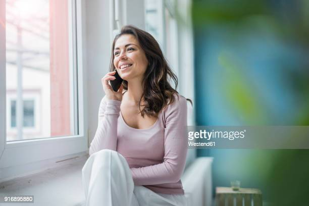 portrait of young woman on the phone looking out of window - am telefon stock-fotos und bilder