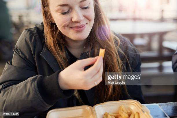 portrait of young woman, outdoors, eating chips, bristol, uk - prepared potato stock pictures, royalty-free photos & images