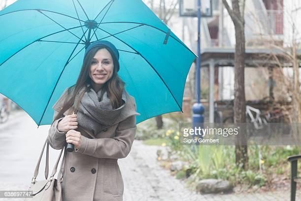 portrait of young woman outdoors, holding blue umbrella - sigrid gombert fotografías e imágenes de stock