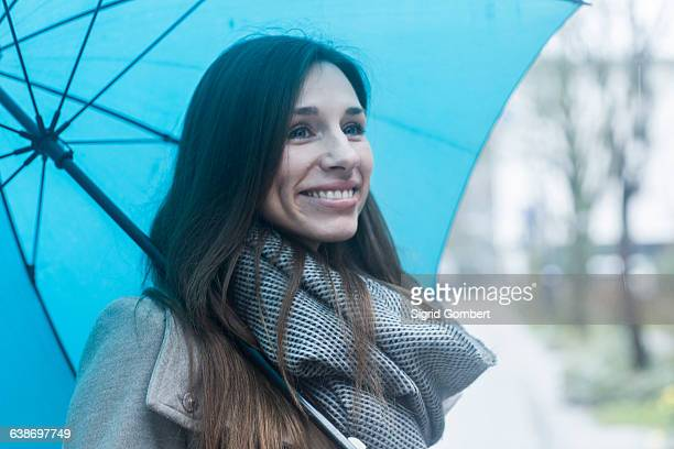 portrait of young woman outdoors, holding blue umbrella - sigrid gombert fotografías e imágenes de stock