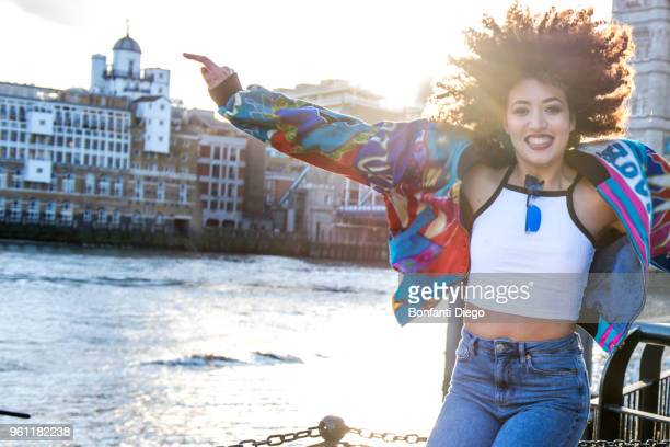 portrait of young woman outdoors, jumping for joy, london, england, uk - crop top stock pictures, royalty-free photos & images