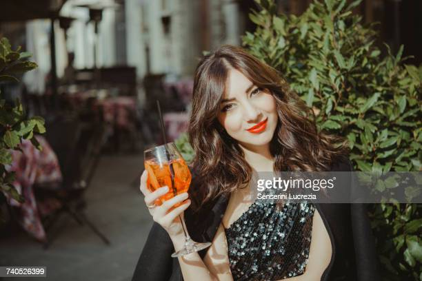 portrait of young woman, outdoors, raising glass - muro stock photos and pictures