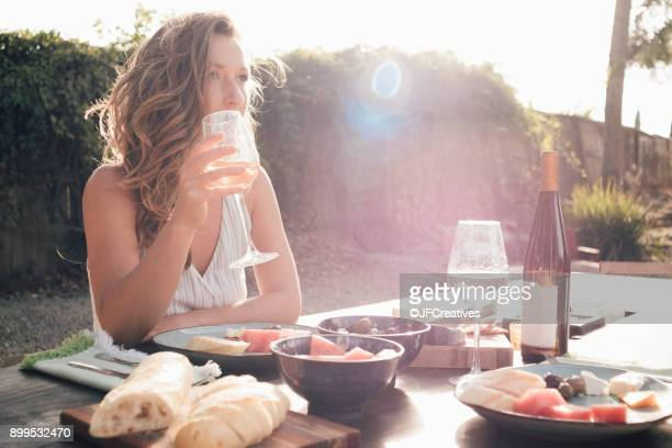 Portrait of young woman, outdoors, sitting at table, holding wine glass