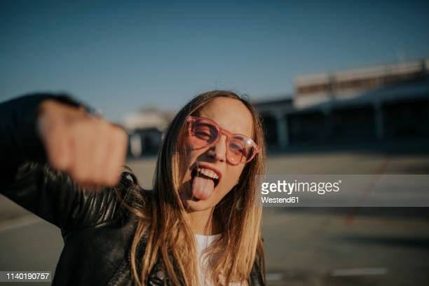 portrait of young woman outdoors sticking out tongue and punching - rébellion photos et images de collection