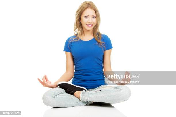 portrait of young woman over white background - cross legged stock pictures, royalty-free photos & images