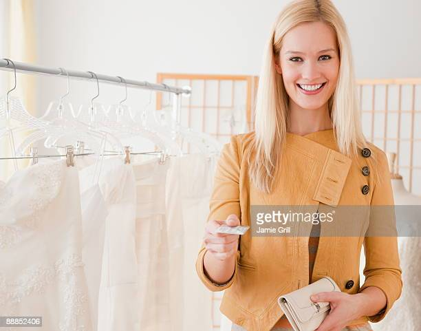 Portrait of young woman paying for wedding dress in bridal shop
