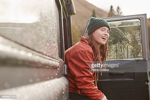 portrait of young woman peering out of car - pluie humour photos et images de collection
