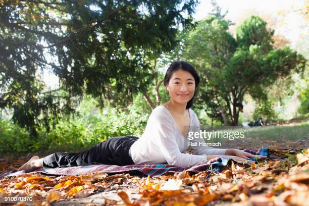 Portrait of young woman performing yoga while lying on picnic blanket against trees at park during a