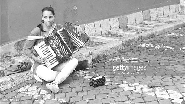 Portrait Of Young Woman Playing Accordion On Street