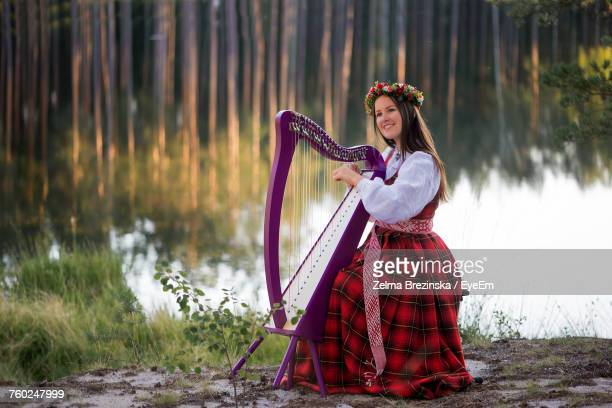Portrait Of Young Woman Playing Instrument By Lake
