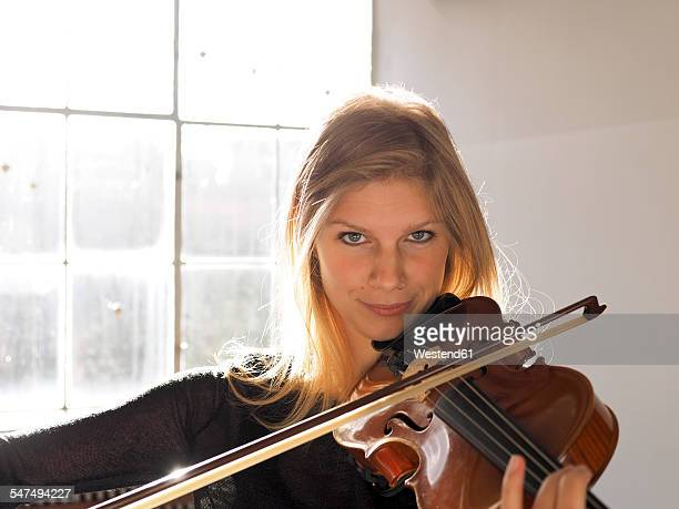 Portrait of young woman playing violin