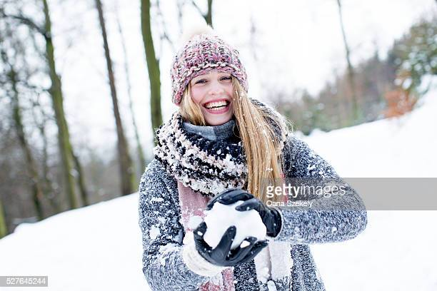 Portrait of young woman playing with snow