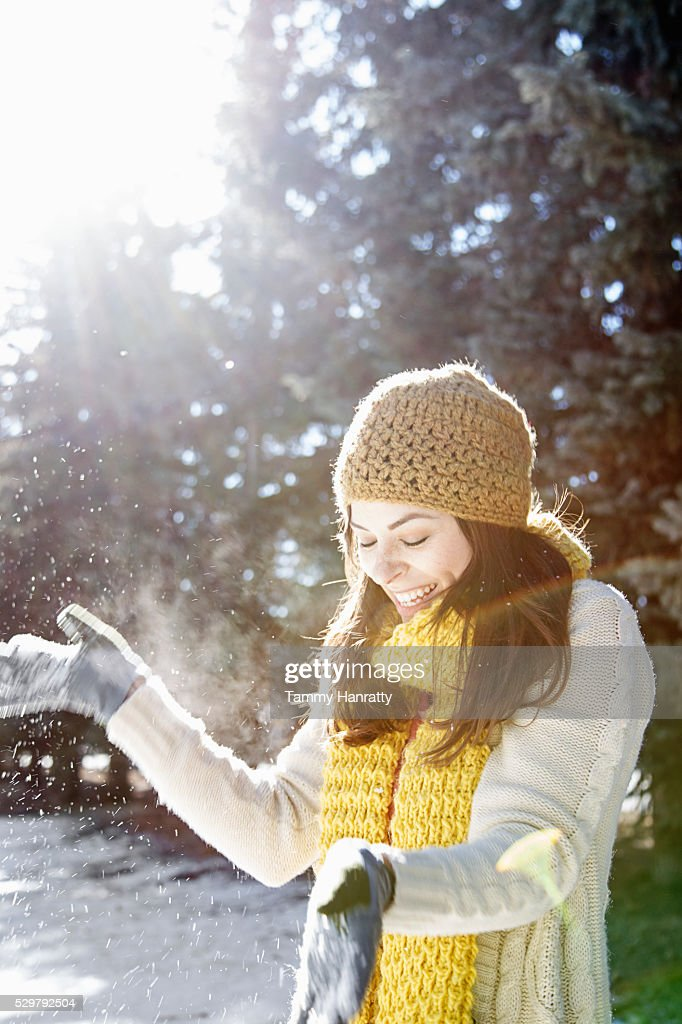 Portrait of young woman playing with snow : Stock-Foto