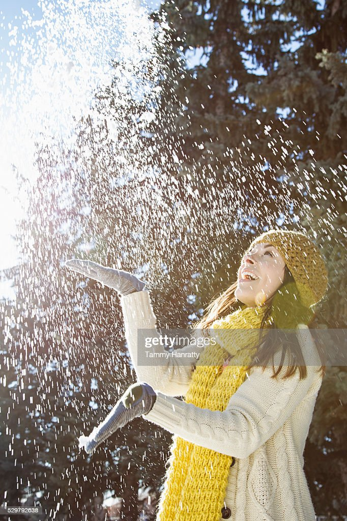 Portrait of young woman playing with snow : Stock Photo
