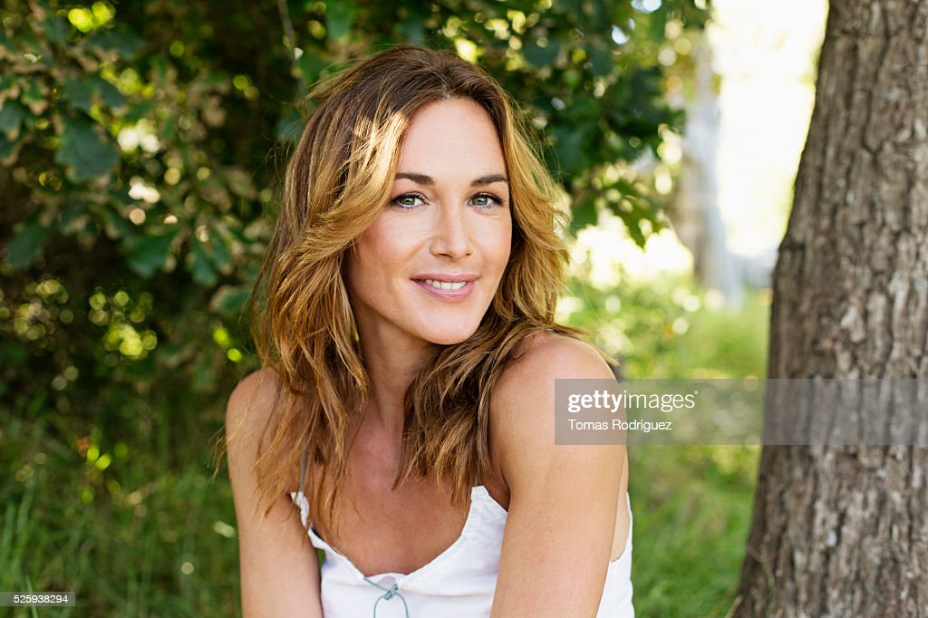 Portrait of young woman posing in park : Stock Photo