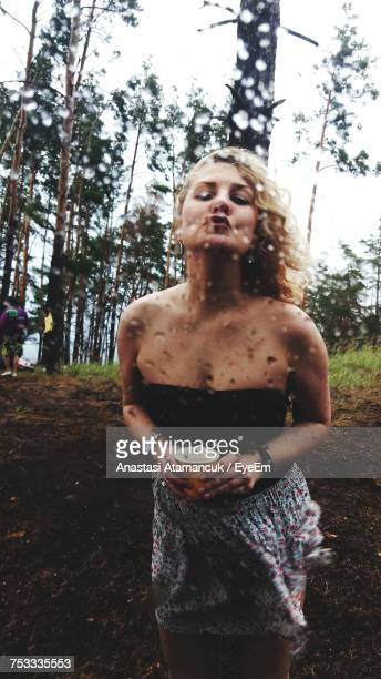 portrait of young woman puckering lips while standing in forest seen through wet glass - damp lips stock photos and pictures