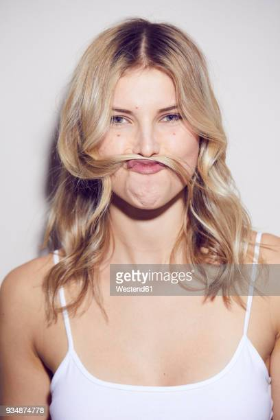 portrait of young woman pulling funny face - cheveux blonds photos et images de collection