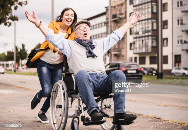 portrait of young woman pushing senior man in wheelchair on pavement - mithilfe stock-fotos und bilder