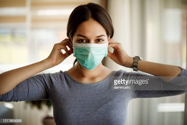 portrait of young woman putting on a protective mask for coronavirus isolation - protective face mask stock pictures, royalty-free photos & images