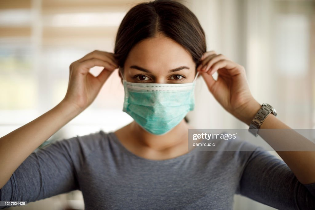 Portrait of young woman putting on a protective mask : Stock Photo