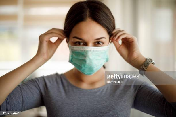 portrait of young woman putting on a protective mask - face masks imagens e fotografias de stock