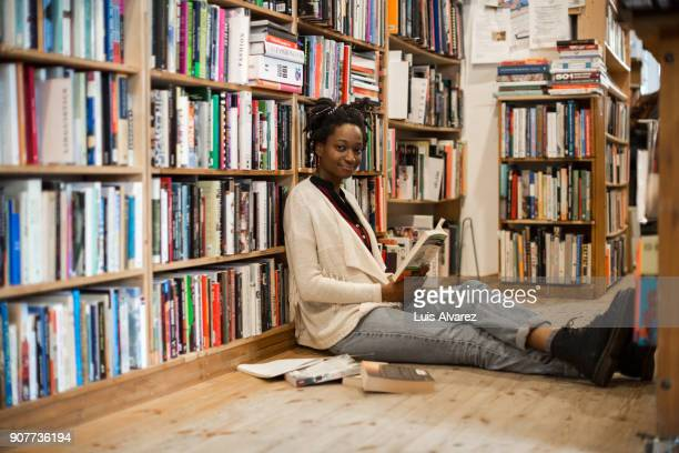 Portrait of young woman reading book while sitting on floor at bookstore