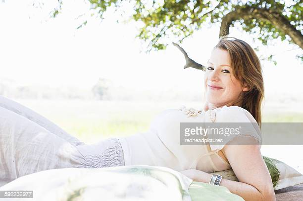 Portrait of young woman reclining on daybed at safari lodge, Kafue National Park, Zambia