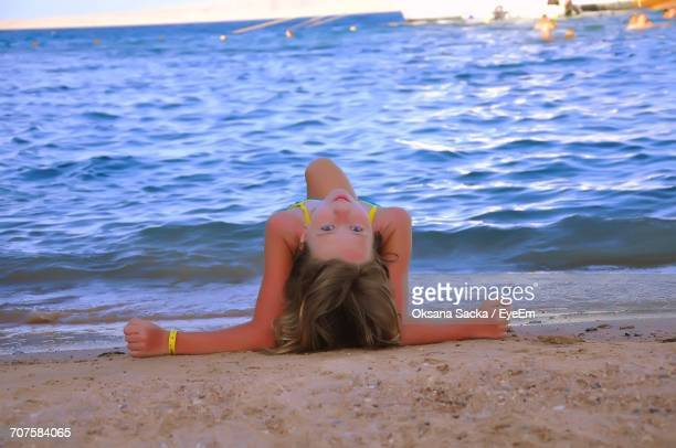 portrait of young woman reclining on sand at beach - seductive women stock pictures, royalty-free photos & images