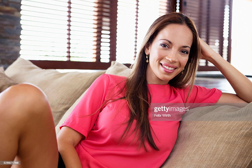 Portrait of young woman reclining on sofa : Stockfoto