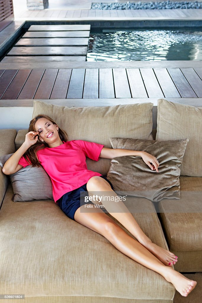 Portrait of young woman reclining on sofa : Photo