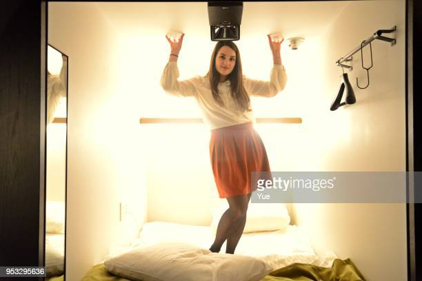 Portrait of young woman relaxing in bed of the capsule hotel