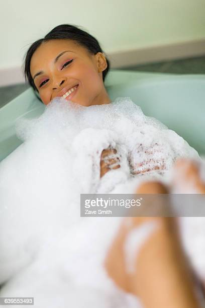 Portrait of young woman relaxing in bubble bath covered in bubbles