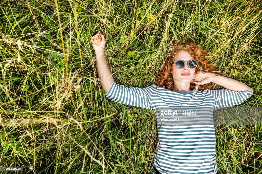 Portrait of young woman relaxing on a meadow : Foto de stock
