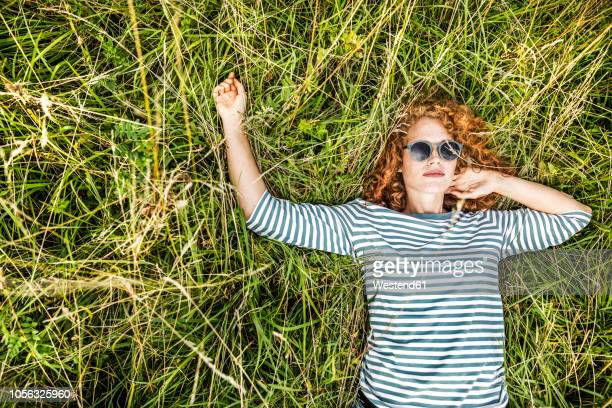 portrait of young woman relaxing on a meadow - lying down foto e immagini stock