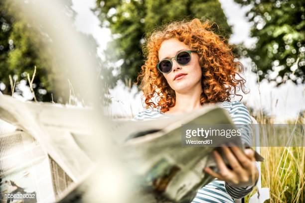 portrait of young woman relaxing on a meadow reading newspaper - einfaches leben stock-fotos und bilder