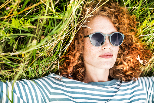 Portrait of young woman relaxing on a meadow wearing sunglasses - gettyimageskorea