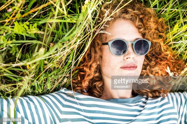 portrait of young woman relaxing on a meadow wearing sunglasses - lying down foto e immagini stock